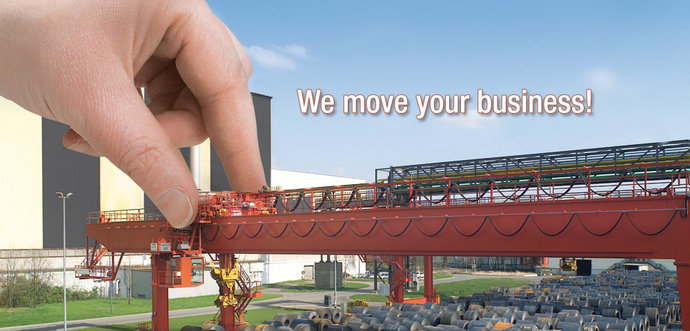 A hand is moving a bridge crane which is equiped with a cable festoon system.